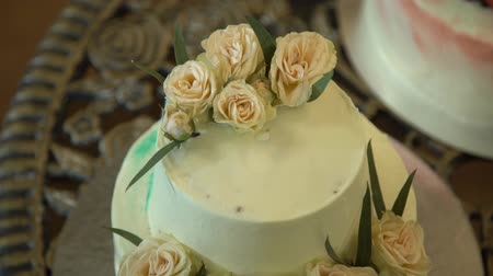 wedding cake : Wedding cake with roses. Beautiful big wedding cake with three storey decorated by tender sweet roses. Outdoor. a white wedding cake with three levels and red roses