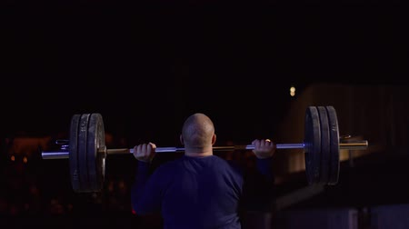 powerlifter : Weightlifter lifts the bar above his head. Strength training with a huge weight. strong crossfit athlete in the middle a heavy snatch lift in a cross-fit box gym