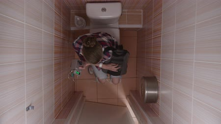 sanitário : Girl in a toilet cubicle with a time machine and a backpack Time machine in the toilet