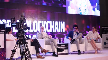 объяснять : DUBAI, UAE - OCTOBER 12, 2017: World blockchain, Speakers Giving a Talk at Business Meeting. Audience in the conference hall. Business and Entrepreneurship. Speakers at Business Conference and Presentation