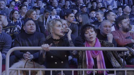 contato com os olhos : Yekaterinburg, Russia - October 2017: Boxers fighting in ring with referee watching. People watching the fight from the stands