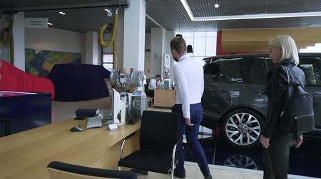 sala de exposição : MOSCOW, RUSSIA - May, 2018: Seller meets customer in dealership. Stock. Woman at car dealer. Vídeos