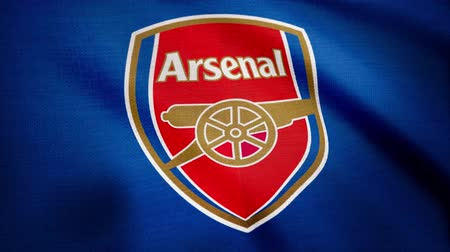 сложить : USA - NEW YORK, 12 August 2018: Animated logo of London football club Arsenal F.C. Close-up of waving flag with Arsenal F.C. football club logo, seamless loop, blue background. Editorial footage