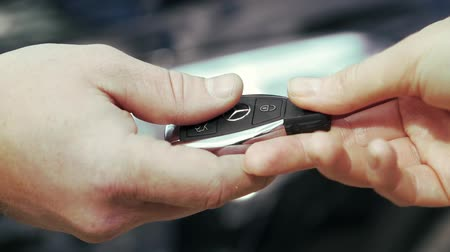 Germany - Berlin, 12 September 2018: Auto business, car sale, deal, gesture and people concept - close up of dealer giving key to new owner and shaking hands in auto show or salon. Stock. Car salesman handing over the keys for a new car Stock Footage
