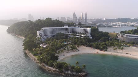 bungaló : SINGAPORE - June, 2018: Top view of houses on the palm beach. Shot. Top view of the sea with palm trees and luxury hotel. Aerial Top view landscape