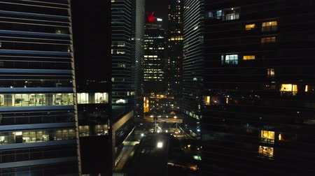 View of a city skyline with skyscrapers in the foreground at night. Shot. Top view of high-rise buildings in center of metropolis at night
