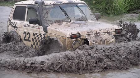 Moscow, Russia - September 2018: Off-road racer rides on muddy deep puddle. Clip. Cars take part in annual off-road races. Close-up of immersion of SUV in puddle Stok Video
