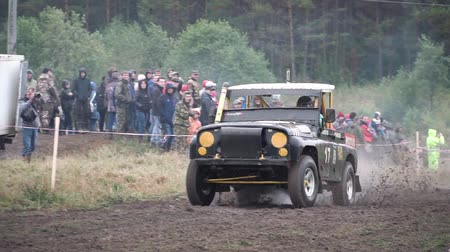 Moscow, Russia - September 2018: Cars take part in annual off-road races. Clip. Close-up of SUVs passing on dirty track on background of fans Stok Video