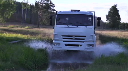 Moscow, Russia - September, 2018: Freight vehicles traveling on country road with puddles. Scene. Truck rides on dusty road and passes puddle in forest. Transportation of rural goods
