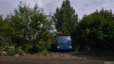 Moscow, Russia - September, 2018: Truck rides on field road in woods. Scene. Truck rides on dusty road among green trees in afternoon. Concept of transportation