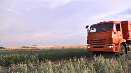 camionagem : Moscow, Russia - September, 2018: Truck goes on rural highway along farm fields. Scene. Close-up of passing orange truck with trailers on rural road in field