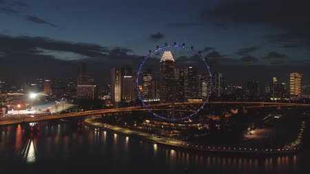 Singapore - 25 September 2018: Aerial view of big city with many lights, cloudy sky, and ferris wheel at night. Shot. Beautiful big city behind the lake at night with a view of a ferris wheel and many buildings. Stok Video