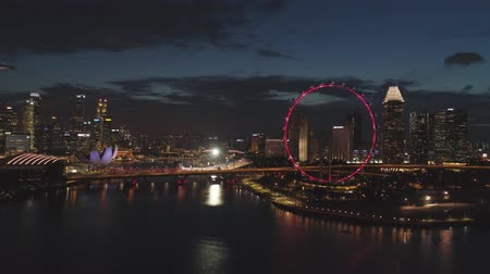 Singapore - 25 September 2018: Singapore cityscape panorama by night with farris wheel behind the river. Shot. Aerial for Singapore night view with bright ferris wheel and the river. Stok Video