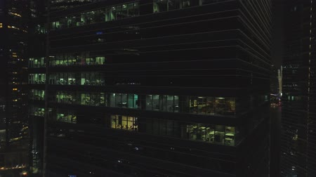Singapore - 25 September 2018: Windows with people working in the interior of an office building at night in big city. Shot. Night big city life, close up for beautiful glass facade skyscraper, concept of business, modern life. Stok Video