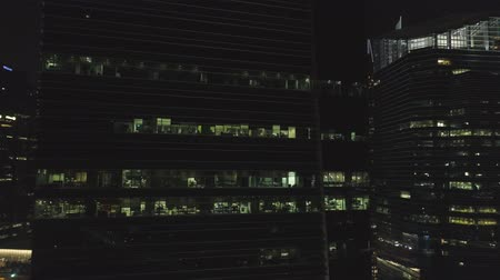 Singapore - 25 September 2018: Windows with people working in the interior of an office building at night in big city. Shot. Night big city life, close up for beautiful glass facade skyscraper, concept of business, modern life. Stock Footage