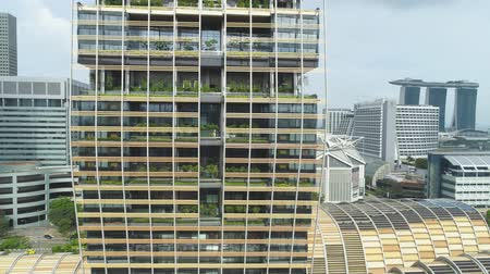 Singapore - 25 September 2018: Close up view for vertical forest building in the center of the city, nature saving concept. Shot. Modern, unusually designed building with many trees on the balconies in big city.