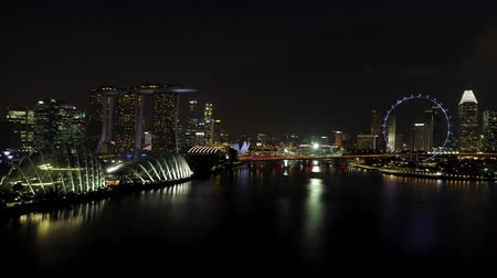 Singapore - 25 September 2018: Singapore by night cityscape panorama with Ferris wheel and Marina Bay Sand, night Singapore life. Shot. Singapore, city that never sleeps, with its bright night illumination.