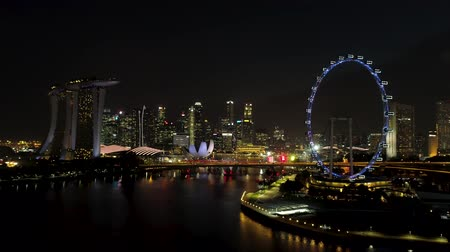 Singapore - 25 September 2018: Singapore city skyline at night with the river, purple lighted Ferris wheel and famous Marina Bay Sands Hotel. Shot. Breathtaking aerial view of night Singapore with Ferris wheel and Marina Bay Sands.