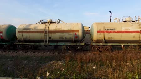 Russia, Moscow - 25 September 2018: Set of tanks with oil and fuel transport by rail. Stock. Cistern of oil on the rails on blue sky and green field background. Stock Footage