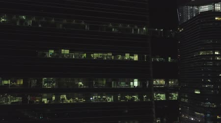 Singapore - 25 September 2018: Frontal view of the night facade of building with a lot of lighted windows. Shot. Facade the multi-storey building of glass and steel, offices and working people inside, night city life background Stok Video