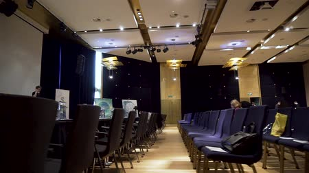 convenção : Great Britain - London, 10 December 2018: Side view of conference hall, rows of blue chairs with battles of water on them against big white projector screen. Stock. Spacious business auditorium with modern equipment.