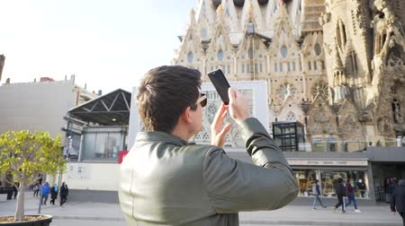 Spain - Barcelona, 12 August 2018: Man in leather jacket and black sun glasses taking photo of the gothic cathedral facade in a sunny day. Stock. Young tourist takes a picture of gothic style cathedral over blue sky background.