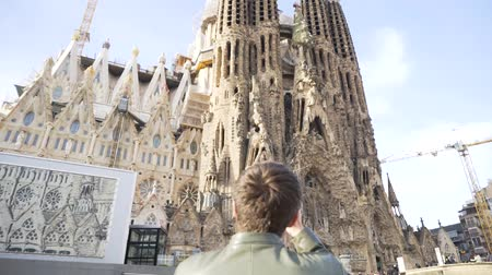 bab : Spain - Barcelona, 12 August 2018: Man in leather jacket and black sun glasses taking photo of the gothic cathedral facade in a sunny day. Stock. Young tourist takes a picture of gothic style cathedral over blue sky background.