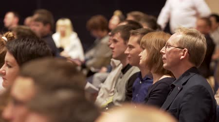 Great Britain - London, 10 December 2018: Close up for interested audience at a business seminar listening to a speaker. Stock. Side view of rows with people in conference hall listening to presenter. Stok Video