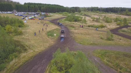Moscow, Russia - September 2018: Extreme off-road car racing. Clip. Top view of off-road race. Event of season in Motorsport. Dirty race with many spectators and fans are on road in forest in cloudy rainy weather