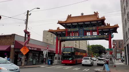 passerby : Seattle historic Chinatown Gate on an overcast day with traffic and onlookers