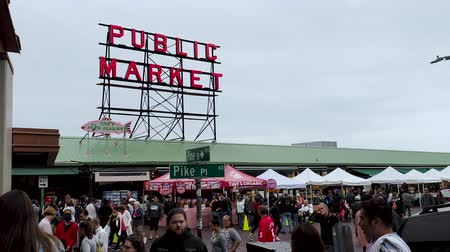 szczupak : Visitors and tourists walk along Seattle Pike Place Market under street sign