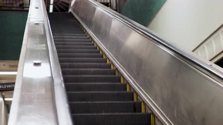 Angled shot of escalator going down in underground subway station Stock Footage