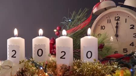 полночь : Countdown to the arrival of the new year with candles with text 2020, clock passing the seconds and festive decoration. Front view.