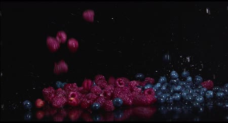 fresco : Raspberries and blueberries on a black background Vídeos