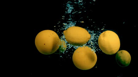 лимон : Citrus fruit in water on a black background