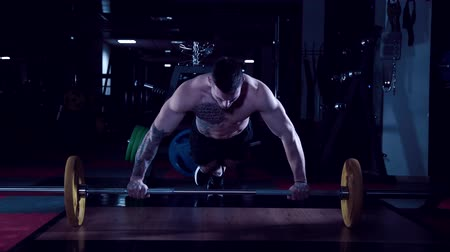 pushed : tattooed male athlete is pushed away from the bar