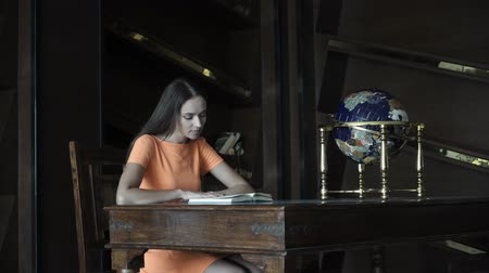 enciclopédia : Beautiful girl reading a book in the library Stock Footage