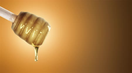 összetevők : Honey dripping from honey dipper on orange background