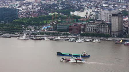 cbd : multiple barges sailing along river through Shanghai. Shanghai, China