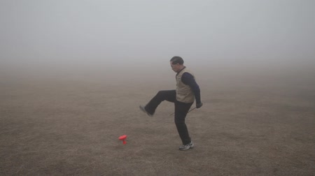 heritage : Man playing diabolo in park hazed by mist in the morning,xian,shaanxi,china