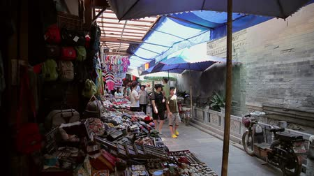 parasol : XIAN, CHINA - MAY 26, 2012: Unidentified people choose traditional souvenirs at the stall at the shopping street in Xian, China.
