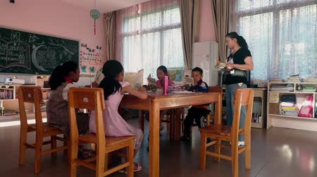 školák : Guangyuan, CHINA - JUNE 04, 2019: Schoolchild and teacher in classroom,China. Dostupné videozáznamy