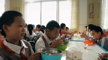 lunchen : Guangyuan, CHINA - JUNE 04, 2019: Children have breakfast in school canteen,China.