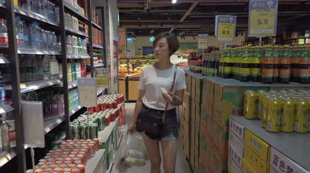 Xian, Shaanxi, China, JUNE 13, 2019. Woman shopping in a supermarket 動画素材
