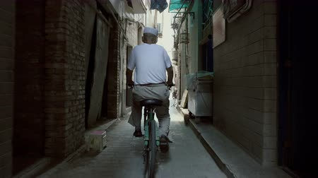 wall building feature : Xian, Shaanxi, China, JUNE 13, 2019. Man ride bicycles in a narrow alley