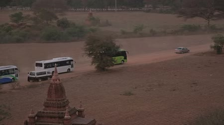 nyaung u : NZAUNG-U, MYANMAR - FEBRUARY 22: Tourist buses leaving after watching the sunset on the pagoda in Bagan on February 22, 2012 in Nyaung-U, Myanmar. Stock Footage