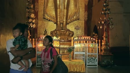 paya : BAGAN, MYANMAR - FEBRUARY 23: Standing Buddha Kassapa at south facing part of the Ananda temple constantly adorned by believers by sticking golden leaves on statue on February 23, 2013 in Bagan, Myanmar. Stock Footage