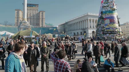Украина : KIEV, UKRAINE - MARCH 22, 2014: People visiting Maidan square to see barricades and Christmas tree covered with messages of support.