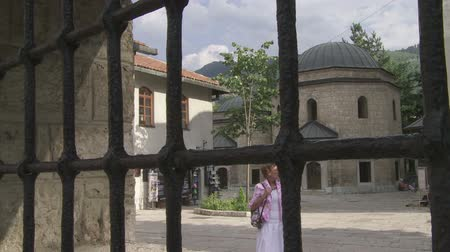 bascarsija : SARAJEVO, BOSNIA AND HERZEGOVINA - FEBRUARY 14, 2013: Tourists sightseeing the Gazi Husrev Beg tomb with a sound of Adhan, a call for prayer. Stock Footage