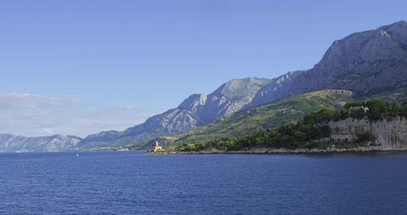 traverse : The lighthouse near Makarska city port in the summer morning.